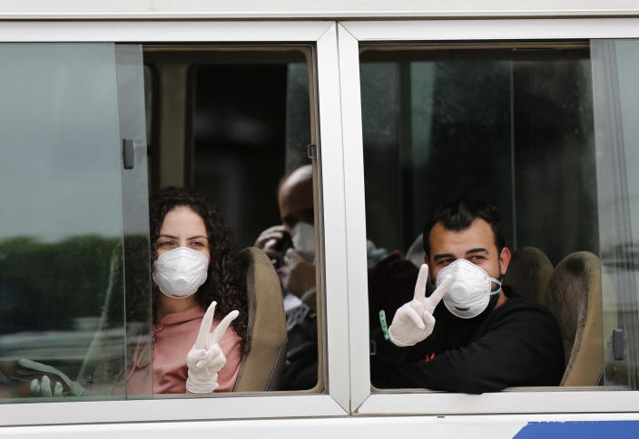 Lebanese passengers who were stuck in Saudi Arabia flash victory signs, as they sit in a bus after arriving to Rafik Hariri Airport, in Beirut, Lebanon, Sunday, April 5, 2020. Passengers who arrived in Lebanon from abroad will be transferred by buses to hotels where they'll get tested for coronavirus. Once the results are known, those who test negative can go home while anyone who tests positive will be referred to local hospitals. A jet carrying more than 70 Lebanese citizens, who had been stuck in Saudi Arabia after Beirut's international airport closed nearly three weeks ago to limit the spread of coronavirus, arrived in Lebanon Sunday. (AP Photo/Hussein Malla)