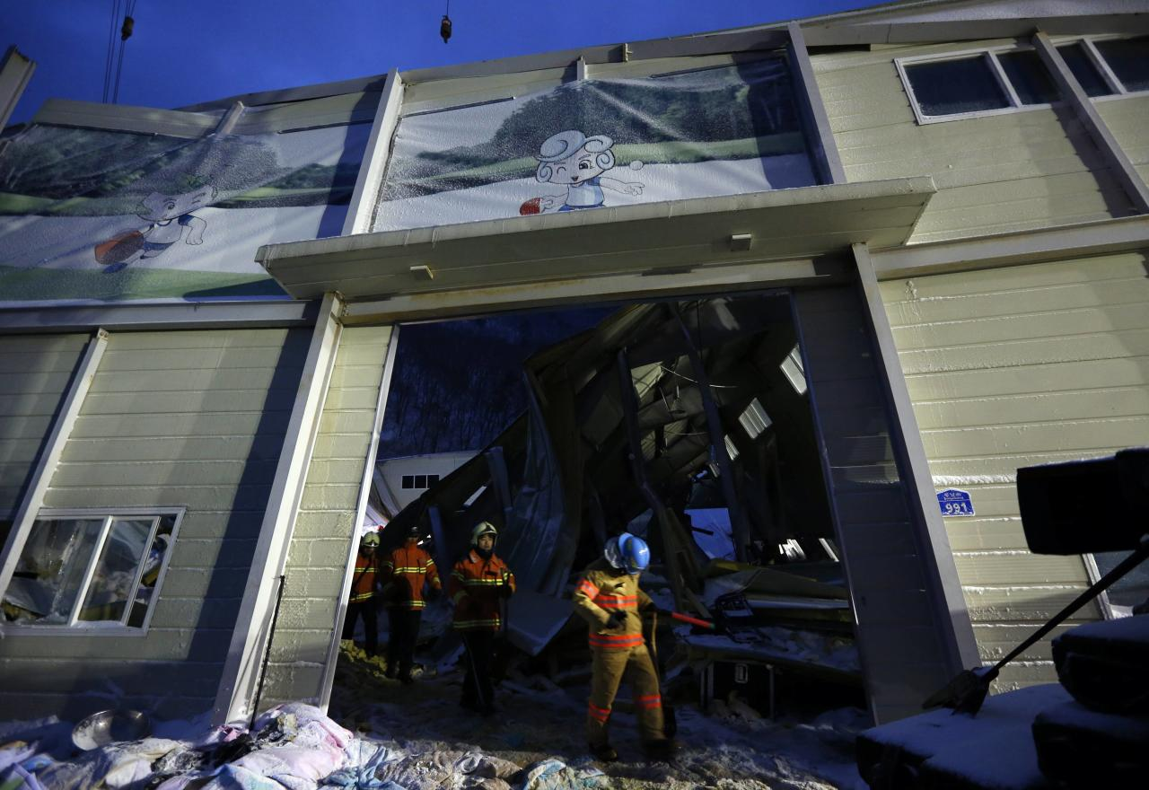 Rescue workers walk out of a collapsed resort building in Gyeongju, about 375 km (235 miles) southeast of Seoul February 18, 2014. Ten people attending a welcoming party for new university students were killed when a building at a South Korean mountain resort collapsed late on Monday, emergency officials said, trapping dozens in snow and rubble for several hours. About 560 students had gathered in the auditorium of the golf resort in the mountains in the city of Gyeongju, around 375 km (235 miles) southeast of Seoul. Heavy snow had built up on the roof of the prefabricated building, causing it to collapse, fire department officials said. REUTERS/Kim Hong-Ji (SOUTH KOREA - Tags: DISASTER TPX IMAGES OF THE DAY)