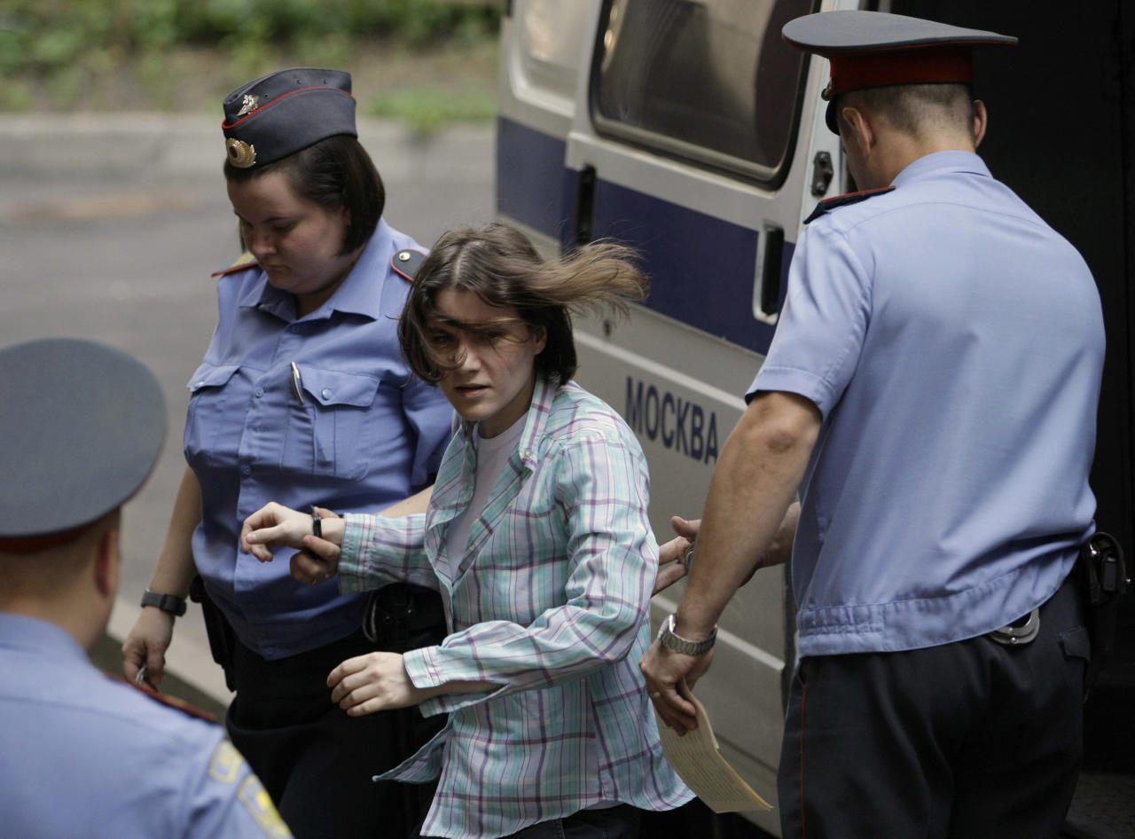 "Maria Alekhina, center, a member of feminist punk group Pussy Riot is escorted to a court room in Moscow, Russia, Monday, July 30, 2012. Three members of the band are facing trial for performing a ""punk prayer"" against Vladimir Putin from a pulpit of Moscow's main cathedral before Russia's presidential election in March, in which he won a third term. (AP Photo/Mikhail Metzel)"