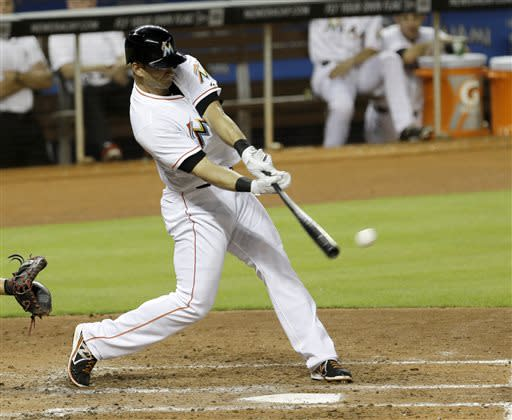 Miami Marlins' Justin Ruggiano hits a base hit against the Atlanta Braves in the fifth inning of a baseball game, Monday, July 8, 2013, in Miami. Adeiny Hechavarria scored on the base hit. (AP Photo/Alan Diaz)