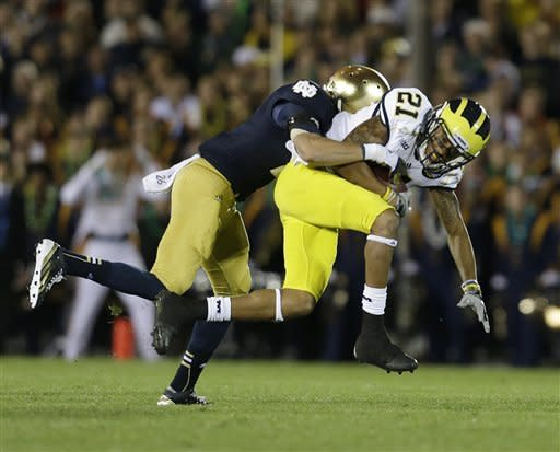 Michigan's Roy Roundtree (21) is tackled by Notre Dame's Bennett Jackson during the first half of an NCAA college football game Saturday, Sept. 22, 2012, in South Bend, Ind. (AP Photo/Darron Cummings)