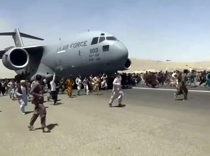 Hundreds of people run alongside a U.S. Air Force C-17 transport plane as it moves down a runway of the international airport, in Kabul, Afghanistan, Monday, Aug.16. 2021.  (Verified UGC via AP)