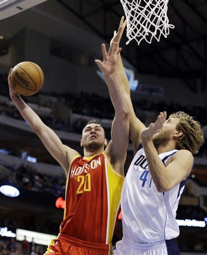 Houston Rockets forward Donatas Motiejunas (20), of Lithuania, shoots as Dallas Mavericks' Dirk Nowitzki (41), of Germany, defends in the first half of an NBA basketball game, Wednesday, March 6, 2013, in Dallas. (AP Photo/Tony Gutierrez)