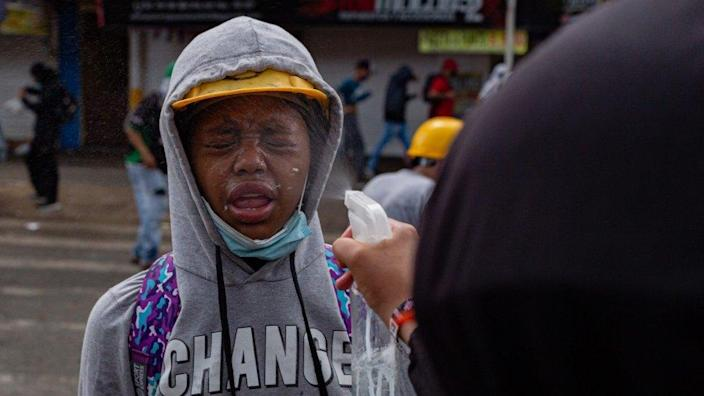 A woman's face is sprayed with vinegar to counteract the effects of tear gas at a protest in Medellín on 2 June 2021