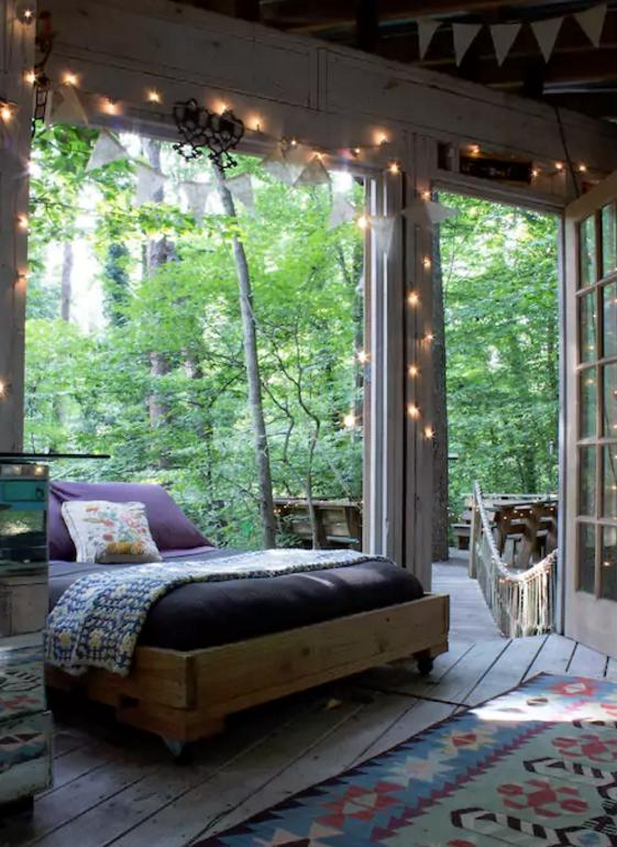 <p>The treehouse consists of a bedroom, living room and a deck, which are all connected by rope bridges. The bedroom features a charming, vintage decor. (Airbnb) </p>