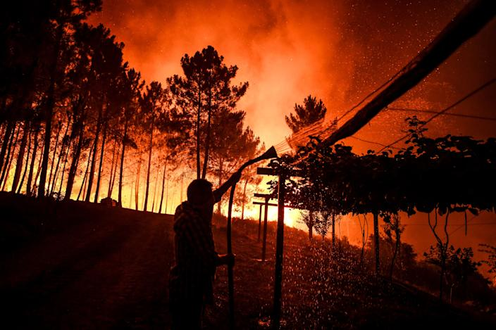 A villager holds a hose as a wildfire comes close to his house at Amendoa in Macao, central Portugal on July 21, 2019. (Photo: Patricia De Melo Moreira/AFP/Getty Images)