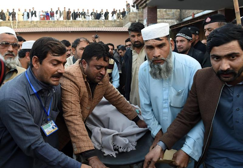 Mourners carry a victim in Mardan, Pakistan, after a Taliban suicide bomber attacked a government office on December 29, 2015 (AFP Photo/A. Majeed)