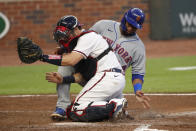 New York Mets' Robinson Cano, rear, is tagged out at home plate by Atlanta Braves catcher Travis d'Arnaud as Cano tried to score on a J.D. Davis base hit during the fourth inning of a baseball game Monday, Aug. 3, 2020, in Atlanta. (AP Photo/John Bazemore)