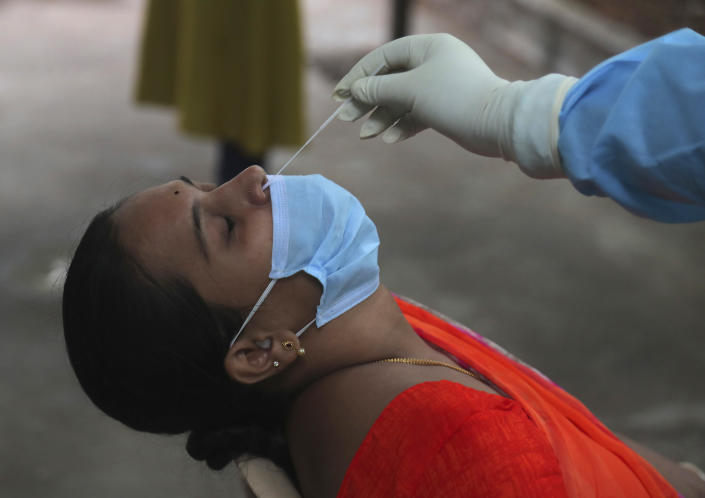 A woman gets nasal swab sample taken to test for the coronavirus at a government health center in Hyderabad, India, Wednesday, July 15, 2020. As India's coronavirus caseload approaches 1 million, lockdowns are being reimposed in parts of the country as governments try to shield the health system from being overwhelmed. (AP Photo/Mahesh Kumar A.)