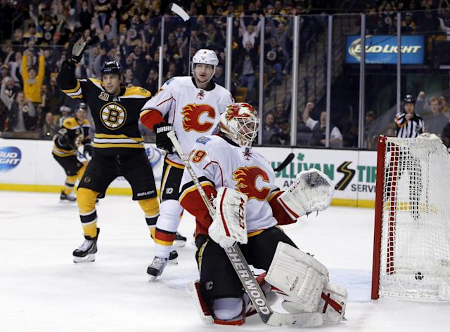 Boston Bruins left wing Milan Lucic, left, celebrates a goal by teammate Zdeno Chara, not seen, as Calgary Flames goalie Reto Berra (29) looks back with defenseman Ladislav Smid (3) during the second period of an NHL hockey game in Boston, Tuesday, Dec. 17, 2013. (AP Photo/Elise Amendola)