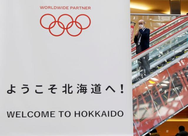 A man wearing protective face mask, following an outbreak of the coronavirus, is seen next to a campaign banner for Tokyo 2020 Olympic Games at New Chitose Airport in Chitose, Hokkaido