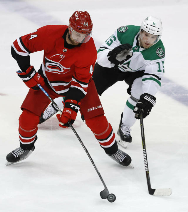 FILE - In this Feb. 23, 2019, file photo, Carolina Hurricanes defenseman Calvin de Haan (44) controls the puck next to Dallas Stars left wing Blake Comeau (15) during the third period of an NHL hockey game in Dallas. The Chicago Blackhawks have acquired de Haan in a trade with the Hurricanes. The Blackhawks also received minor league forward Aleksi Saarela from the Hurricanes in exchange for defenseman Gustav Forsling and goaltender Anton Forsberg. (AP Photo/LM Otero, File)