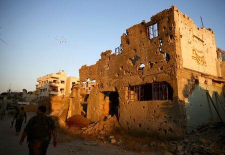 Fighters from the Free Syrian Army's Al Rahman legion walk past damaged buildings in the rebel held Jobar, a suburb of Damascus