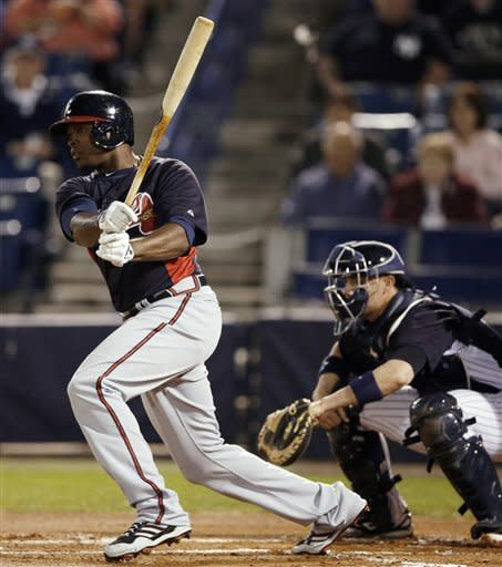 Atlanta Braves' Justin Upton follows through on an RBI ground-out off New York Yankees' David Phelps during the first inning of a spring training baseball game, Tuesday, March 5, 2013, in Tampa, Fla. At right is Yankees catcher Chris Stewart. (AP Photo/Matt Slocum)