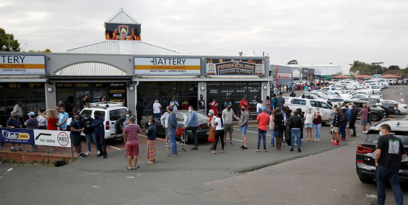 People queue to buy food at a supermarket with most stores staying closed as protests continue following imprisonment of former South Africa President Jacob Zuma in Hillcrest
