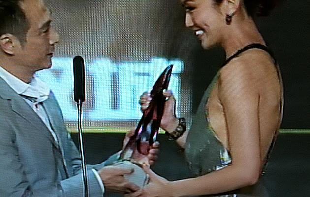 Joanne Peh receives her Best Actress Trophy in a daring backless dress (Youtube Screengrab)