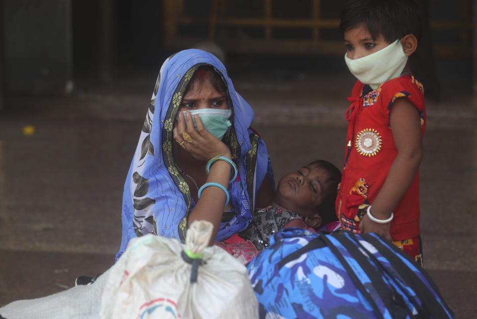 A woman along with her children wait for a train at Lokmanya Tilak Terminus in Mumbai, India, Wednesday, April 7, 2021. India hits another new peak with 115,736 coronavirus cases reported in the past 24 hours with New Delhi, Mumbai and dozens of other cities imposing night curfews to check the soaring infections. (AP Photo/Rafiq Maqbool)
