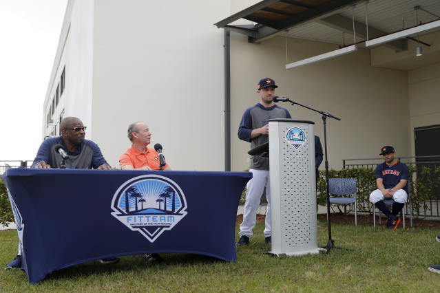Houston Astros' Alex Bregman delivers a statement from the podium as teammate Jose Altuve, seated at right, listens along with manager Dusty Baker, left, and owner Jim Crane, second from left, during a news conference before the start of the first official spring training baseball practice for the team Thursday, Feb. 13, 2020, in West Palm Beach, Fla. (AP Photo/Jeff Roberson)