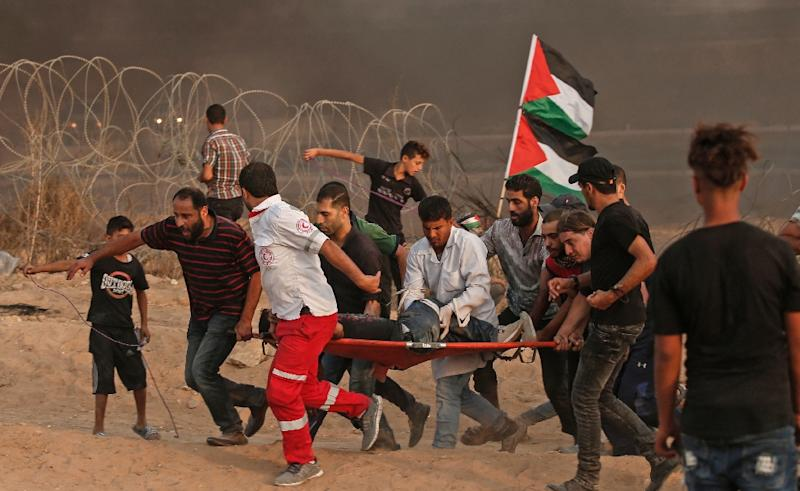 Palestinian paramedics carry an injured protester during a demonstration near the border with Israel, east of Gaza City, on October 19, 2018 (AFP Photo/MAHMUD HAMS)