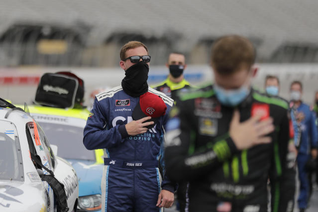 Ryan Sieg, left, stands during the national anthem in pit row before a NASCAR Xfinity Series auto race at Atlanta Motor Speedway, Saturday, June 6, 2020, in Hampton, Ga. (AP Photo/Brynn Anderson)