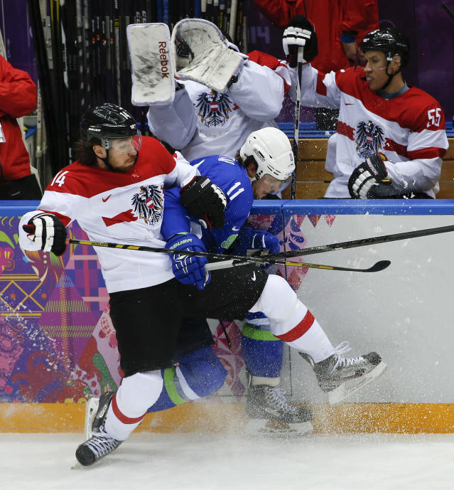 Austria forward Andreas Nodl collides with Slovenia forward Anze Kopitar in the first period of a men's ice hockey game at the 2014 Winter Olympics, Tuesday, Feb. 18, 2014, in Sochi, Russia. (AP Photo/Julio Cortez)