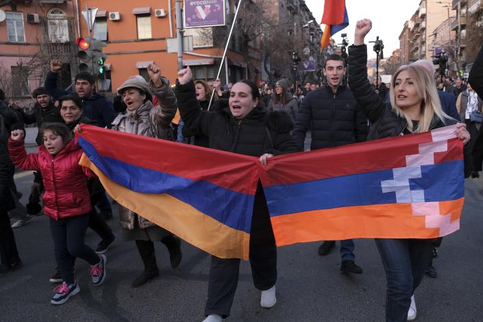 Opposition demonstrators carrying Armenian national and the separatist region of Nagorno-Karabakh's flag, right, march to the government buildings during a rally to pressure Armenian Prime Minister Nikol Pashinyan to resign in Yerevan, Armenia, Saturday, Feb. 27, 2021. The developments come after months of protests sparked by the nation's defeat in the Nagorno-Karabakh conflict with Azerbaijan. (Hrant Khachatryan/PAN Photo via AP)