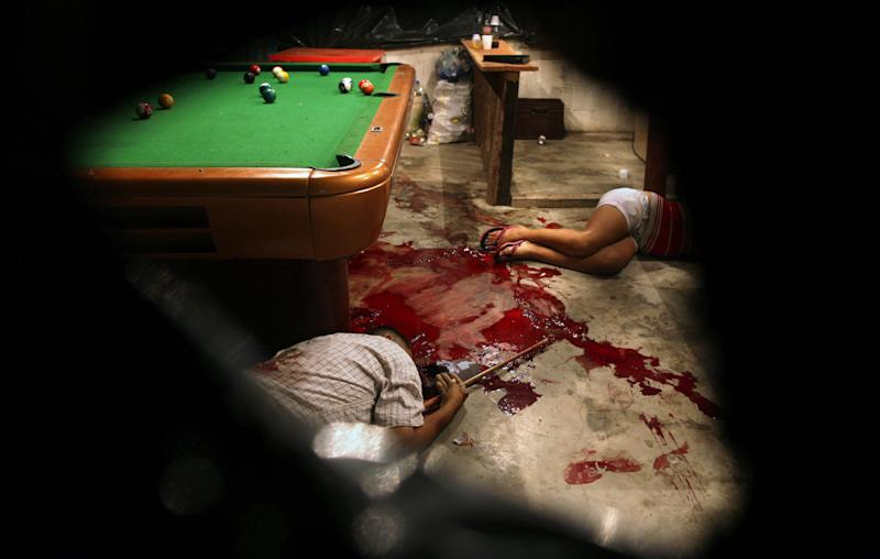 In this March 11, 2012 photo, the bodies of Lesbia Altamirano and Wilmer Orbera lie on the floor of a pool hall after being attacked by unidentified masked assailants in Choloma on the outskirts of San Pedro Sula, Honduras.  A wave of violence has made Honduras among the most dangerous places on Earth, with a homicide rate roughly 20 times that of the U.S. rate, according to a 2011 United Nations report. (AP Photo/Esteban Felix)
