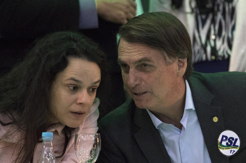Brazil's presidential candidate Jair Bolsonaro, right, talks to lawyer Janaina Paschoal during the National Social Liberal Party convention where he accepted the party's nomination in Rio de Janeiro, Brazil, Sunday, July 22, 2018. The far-right congressman is running in distant second to former President Luiz Inacio Lula da Silva, who is in jail, and promises to clean house ahead of October elections. (AP Photo/Leo Correa)