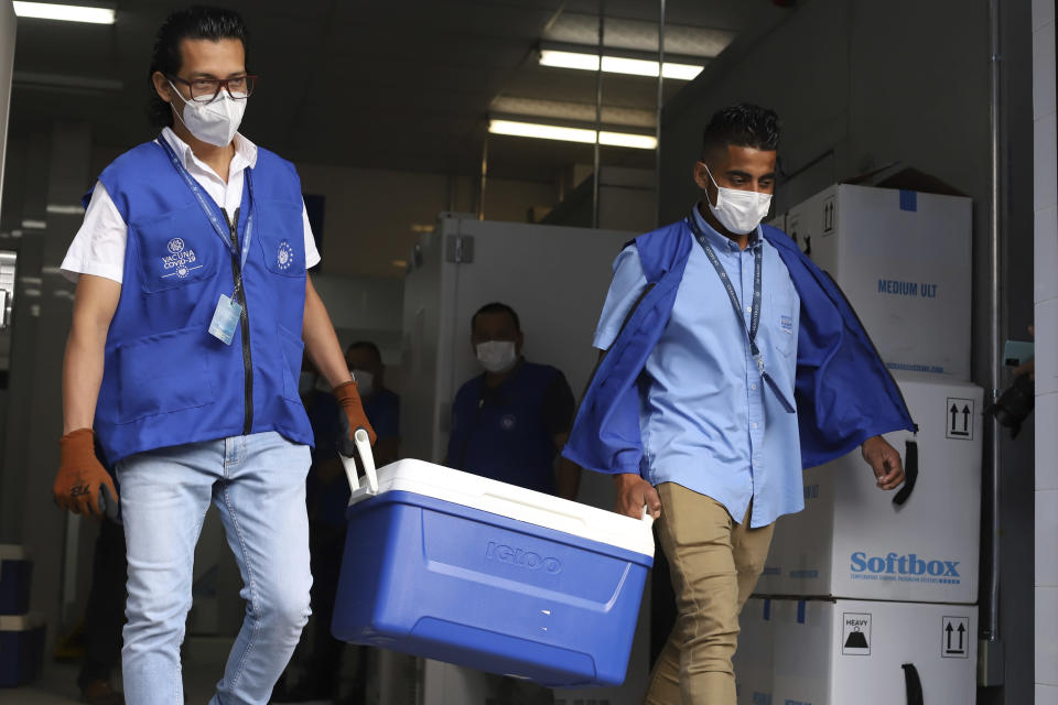 Health Ministry workers carry coolers of COVID-19 vaccines that El Salvador's government is donating to Honduras as they load trucks that will depart San Salvador, El Salvador, Thursday, May 13, 2021. (AP Photo/Salvador Melendez)
