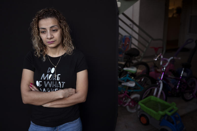 Issis Zavala, of Honduras, poses for a picture Thursday, May 7, 2020, in Carlsbad, Calif. Zavala was detained at the Otay Mesa Detention Center before being released with an ankle bracelet. The early absence of facial coverings, lack of cleaning supplies and mixing symptomatic detainees with others preceded the first big outbreak at U.S. Immigration and Customs Enforcement's 221 detention centers. While the point of origin is unclear, accounts of how the virus spread at the Otay Mesa Detention Center expose shortcomings and inherent difficulties of managing the world's largest immigration detention system during a pandemic. (AP Photo/Gregory Bull)