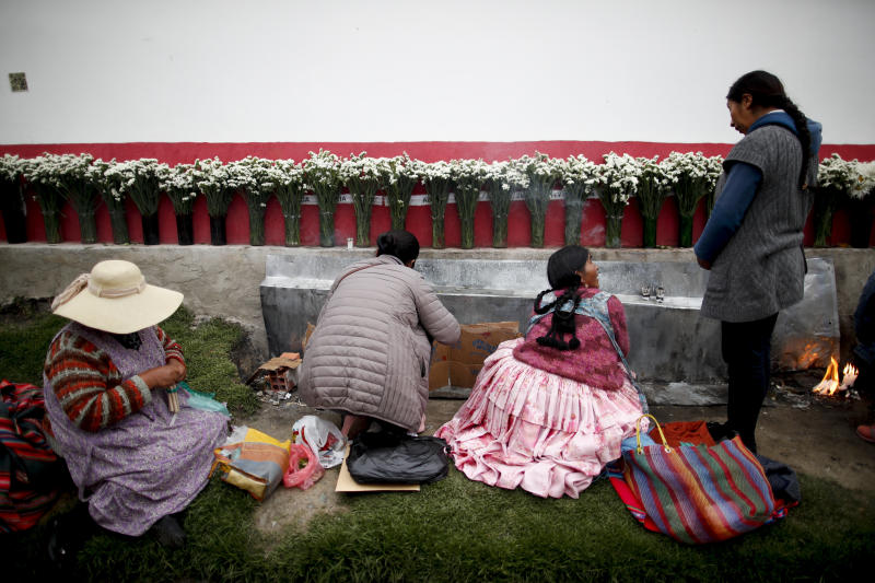 In this picture taken Jan. 7, 2020, women sit at the edge of a cemetery in La Paz, Bolivia, paying homage to unidentified deceased loved ones, who they call the forgotten souls. The women light candles, throw coca leaves and cigarettes bunched together in the traditional indigenous blessing. (AP Photo/Natacha Pisarenko)