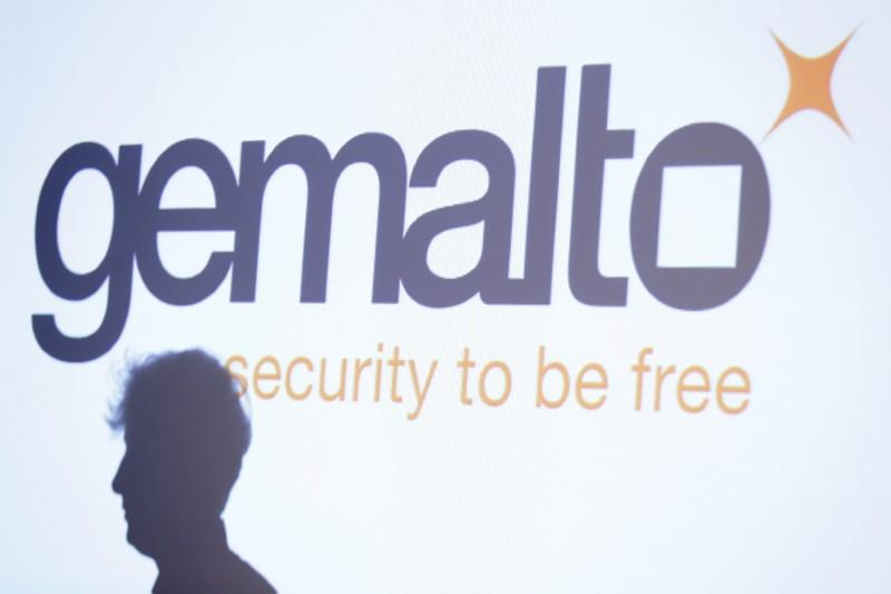 The shadow of an attendee is cast below a logo of Franco-Dutch technology firm Gemalto during a news conference in Paris