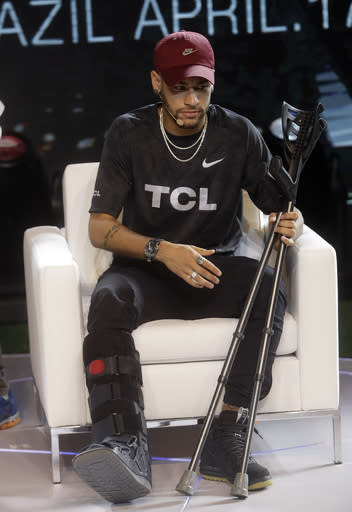 Brazil's soccer star Neymar holds his crutches during a promotional event from one of his sponsors, in Sao Paulo, Brazil, Tuesday, April 17, 2018. The Paris Saint-Germain striker had been found to have suffered a sprain of the right ankle and fissure of the fifth metatarsal after a tangle with Marseille player, Bouna Sarr during a Feb. 25 match. (AP Photo/Andre Penner)