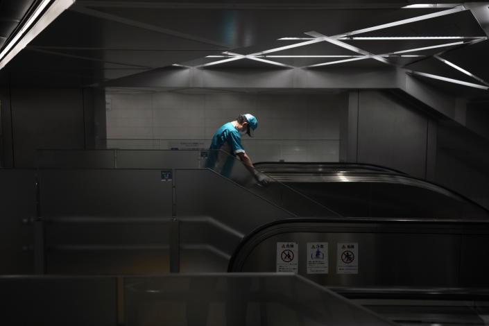 An employee wearing a protective mask to help curb the spread of the coronavirus cleans the handrail of an escalator at the underneath of a subway station Thursday, July 29, 2021, in Tokyo. (AP Photo/Eugene Hoshiko)