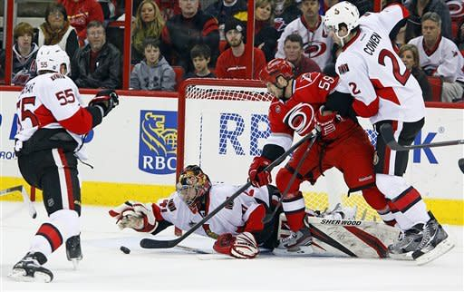 Ottawa Senators goalie Craig Anderson (41) dives on the puck after a shot from Carolina Hurricanes' Chad LaRose (59) as Senators Jared Cowen (2) and Sergei Gonchar (55), of Russia, look on during the first period of an NHL hockey game in Raleigh, N.C., Friday, Dec. 23, 2011. (AP Photo/Karl DeBlaker)