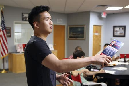 """Calvin Lee, executive director for the Art Alas for Congress campaign, speaks with a flyer in hand at a meeting of so-called """"Liberty Kids"""" libertarian Republican activists in Burbank, California, July 27, 2014. REUTERS/David McNew"""