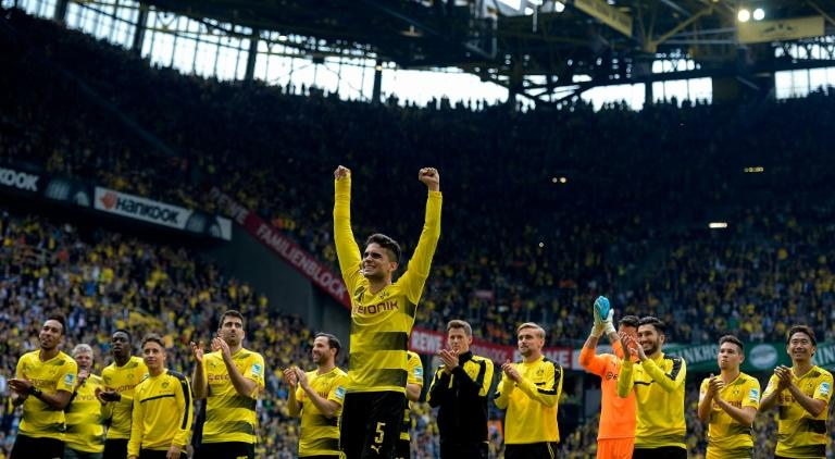 Dortmund's defender Marc Bartra (C) celebrates with his teammates after a German first division football match against Werder Bremen in Dortmund, western Germany, on May 20, 2017