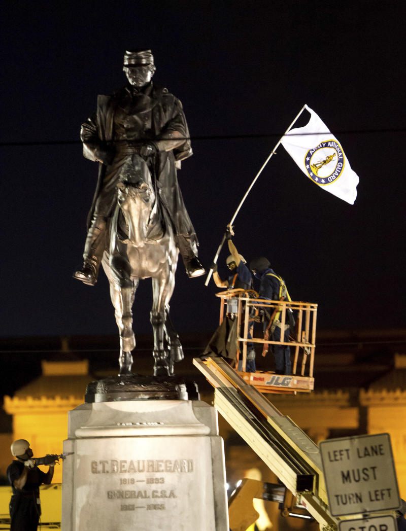 A worker in protective gear takes down an Army National Guard flag from the statue of Confederate General P.G.T. Beauregard during the statue's removal from the entrance to City Park in New Orleans, Tuesday, May 16, 2017. The city announced late Tuesday that it had begun the process of removing a statue of Confederate Gen. P.G.T. Beauregard — the third of four monuments city officials plan to take down across the city.  (AP Photo/Scott Threlkeld)