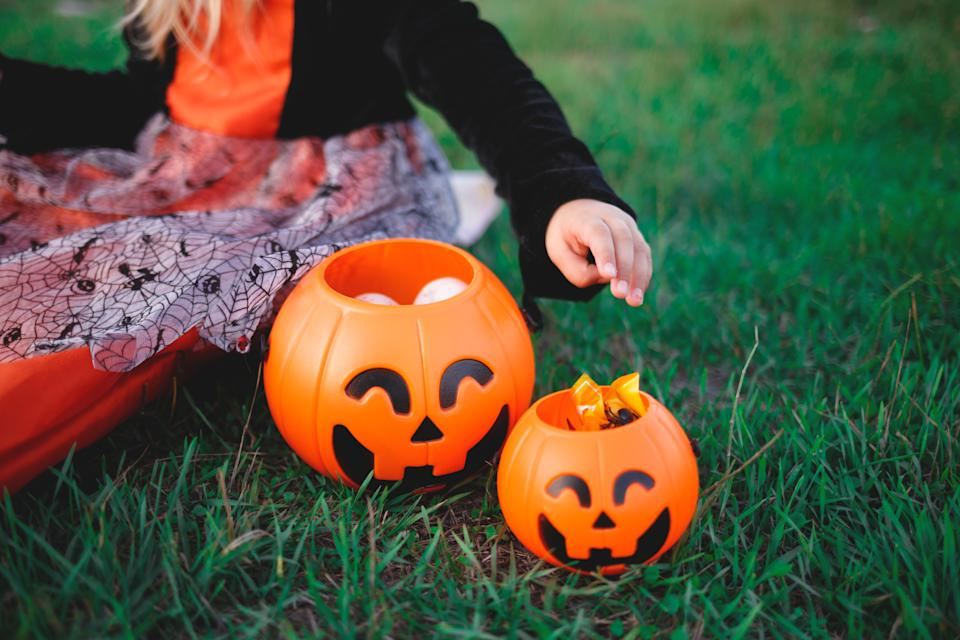 a child's hand reaches for candy in a pumpkin-shaped candy basket.