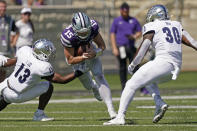 Kansas State quarterback Will Howard (15) runs between Nevada defensive back Jordan Lee (13) and linebacker Lawson Hall (30) during the first half of an NCAA college football game Saturday, Sept. 18, 2021, in Manhattan, Kan. (AP Photo/Charlie Riedel)