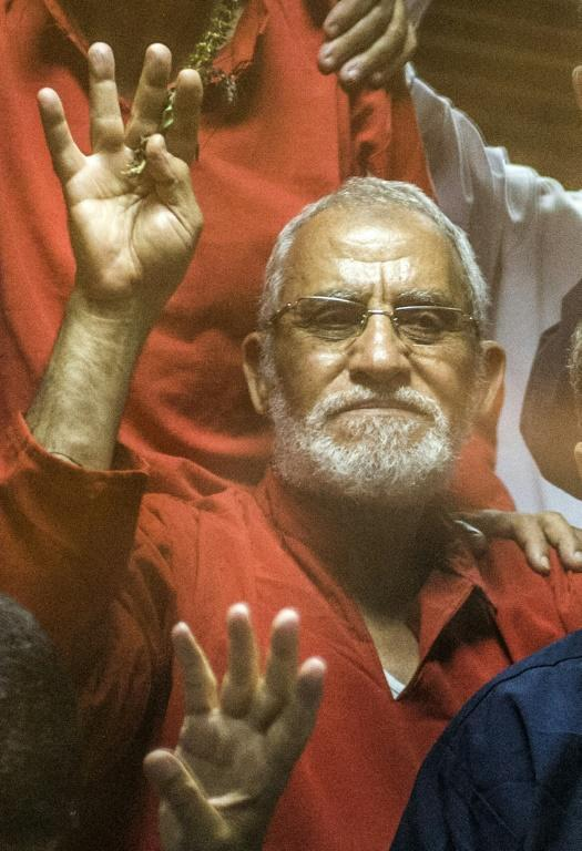"""Egyptian Muslim Brotherhood leader Mohamed Badie (C) flashes the four finger symbol known as """"Rabaa"""" from behind the defendant's cage as the judge reads out the verdict sentencing him and more than 100 other defendants on May 16, 2015"""