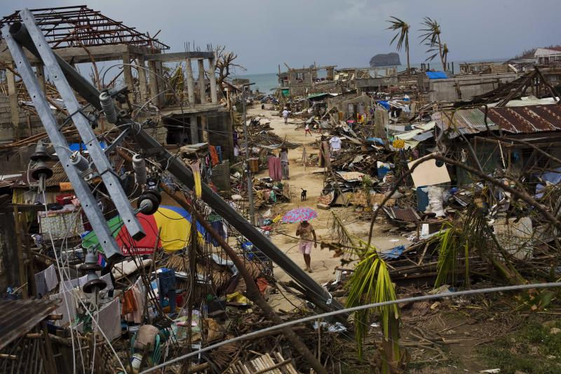 FILE - In this Nov. 14, 2013 file photo, Typhoon Haiyan survivors walk through ruins in the village of Maraboth, in the Philippines. Last year was tied for the fourth warmest year on record around the world. The National Oceanic and Atmospheric Administration on Tuesday released its global temperature figures for 2013. The average world temperature was 58.12 degrees (14.52 Celsius) tying with 2003 for the fourth warmest since 1880.(AP Photo/David Guttenfelder)