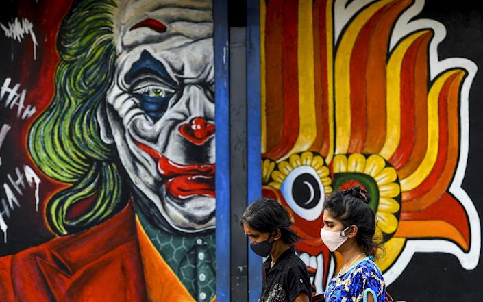 Women walk past a mural painting in Minuwangoda on the outskirts of the Sri Lankan capital of Colombo - AFP