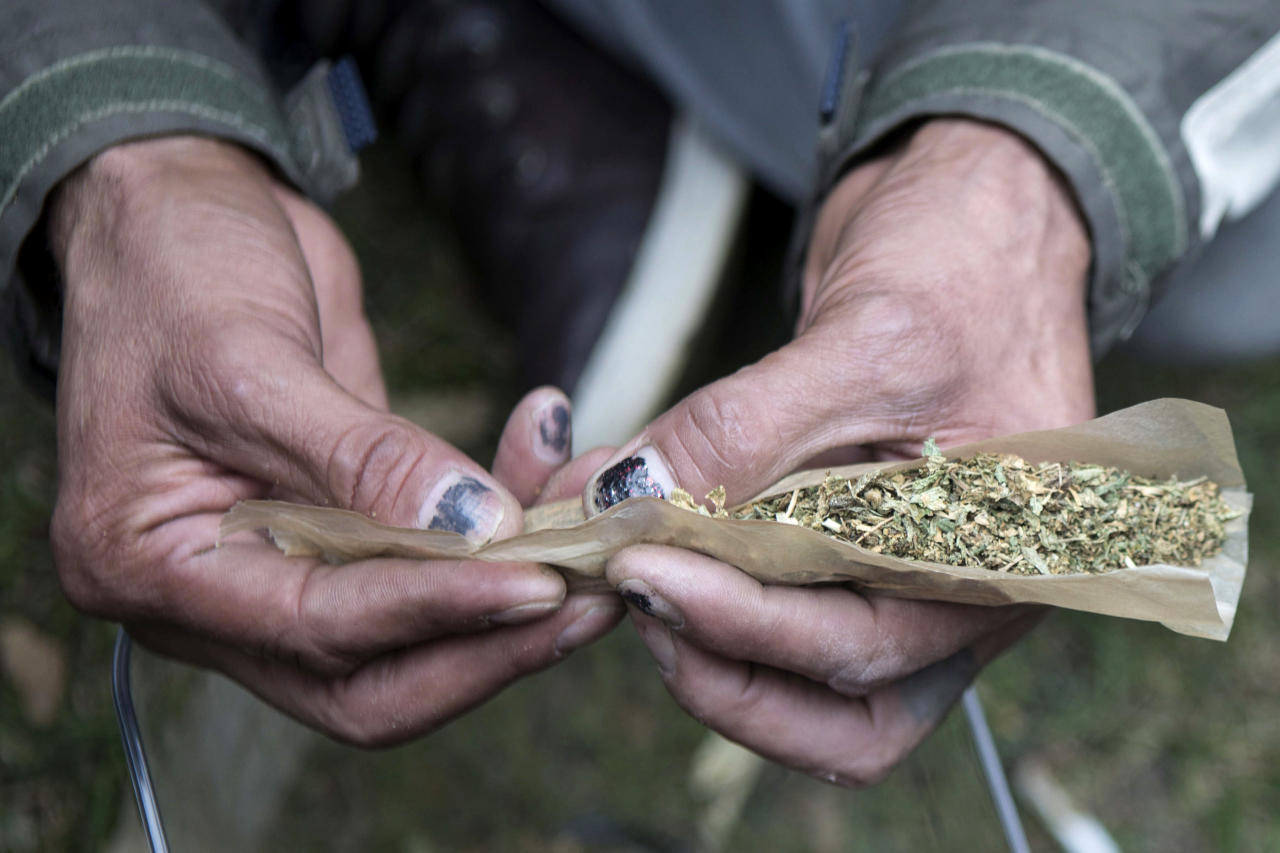A man rolls a large joint in a Toronto park on Wednesday, Oct. 17, 2018. Canada became the largest country with a legal national marijuana marketplace as sales began early Wednesday. (Chris Young/The Canadian Press via AP)