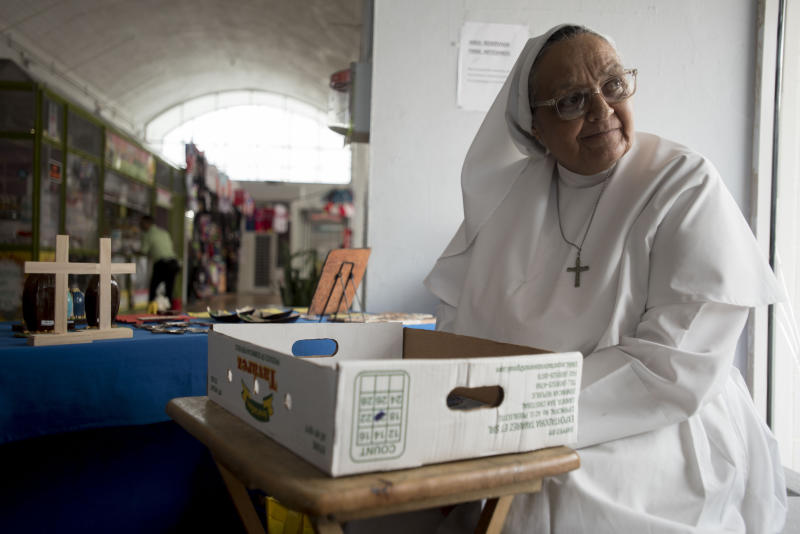 Sister Carmen Negrón, 64, sells handmade rosaries and religious icons in the Plaza del Mercado in San Juan, Puerto Rico, Wednesday, April 17, 2019. Negrón says she's noticed a drop in sales due to what seem to be fewer people in the area. (AP Photo/Carlos Giusti)