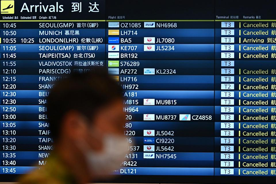 A man walks past a signboard displaying cancelled flights at an arrivals floor of the international terminal at Haneda airport in Tokyo: AFP via Getty Images