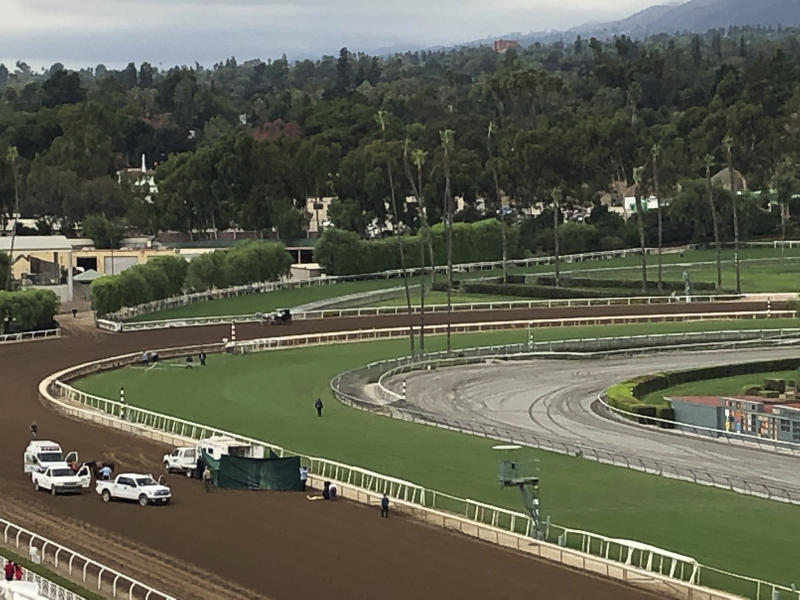 Track personnel attend Emtech, a 3-year-old colt, after he went down in the stretch at Santa Anita on Saturday. The colt as euthanized, marking the 32nd death at the racetrack since December.
