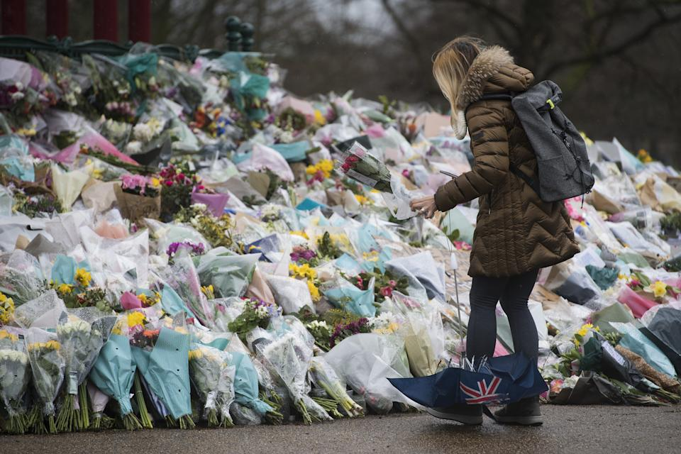 A woman lays flowers at the bandstand in Clapham Common, London, for Sarah Everard. Pc Wayne Couzens, 48, appeared at the Old Bailey in London charged with the kidnap and murder of the 33-year-old. Picture date: Tuesday March 16, 2021.