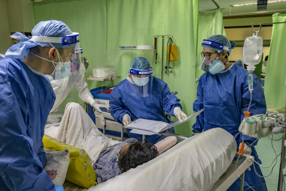 Perlin Bon (right), a nurse, assists a patient while wearing personal protective equipment (PPE) at the pneumonia ward of the National Kidney and Transplant Institute, a government hospital, on April 27, 2021 in Quezon City, Metro Manila, Philippines. (Photo: Ezra Acayan/Getty Images)
