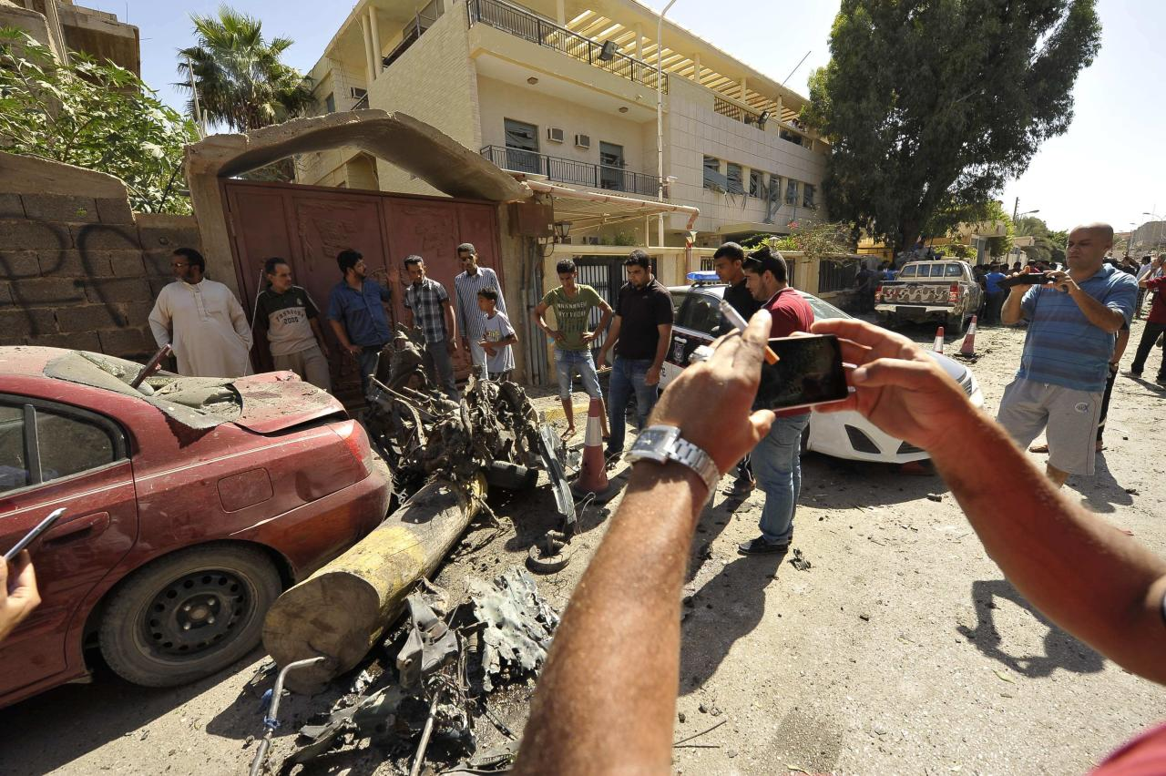 People take pictures of the wreckage of a car after it exploded outside the Swedish consulate in Benghazi October 11, 2013. A car bomb exploded outside the Swedish consulate in the eastern Libyan city of Benghazi on Friday, damaging the building's front and nearby houses, but no casualties were immediately reported, a Reuters witness said. REUTERS/Esam Omran Al-Fetori (LIBYA - Tags: POLITICS CIVIL UNREST)